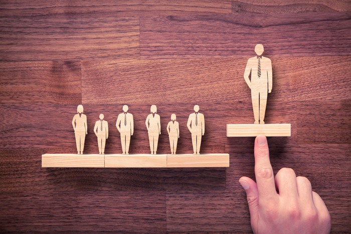 One wooden figure in a group is pushed highr than the others.