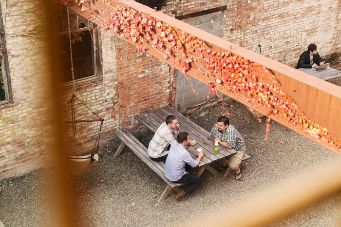 Employees sitting at a picnic table outside Etsy's offices
