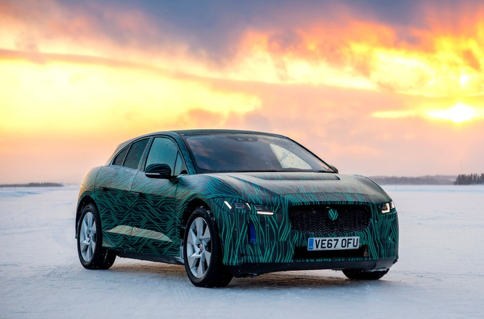 A Jaguar I-Pace, in a green camouflage wrap, parked on snow during testing in northern Sweden.