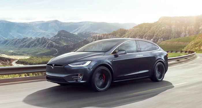 A black Tesla Model X SUV on a mountain road.