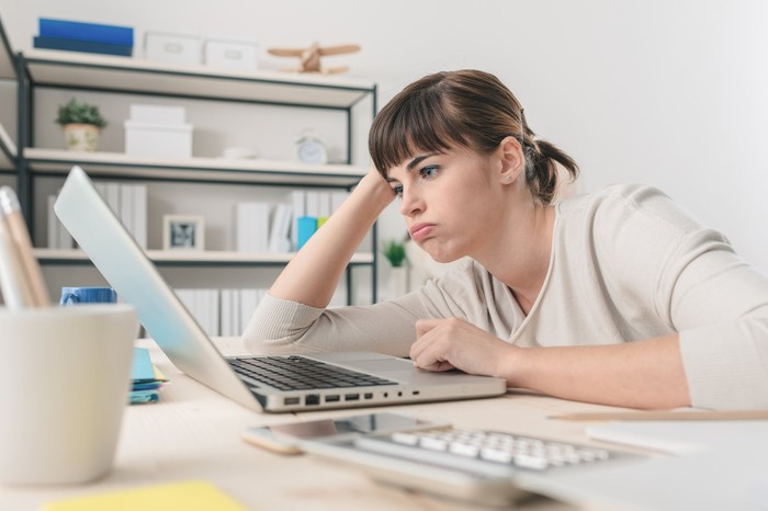 Woman looking at laptop with bored expression.