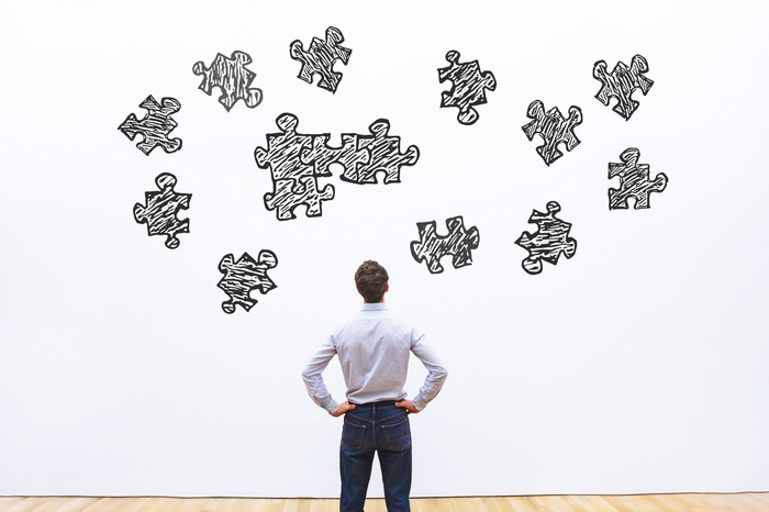 Man in white shirt and blue slacks watching a wall mural of several puzzle pieces, only some of which are fitting together.