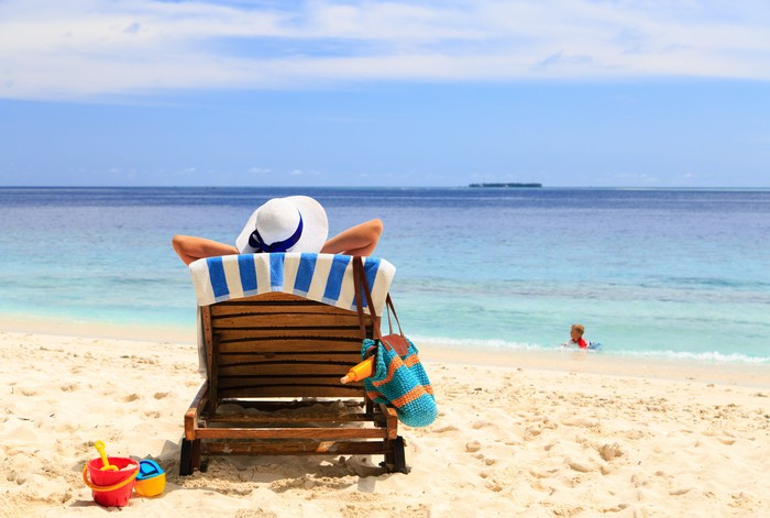 A woman sitting in a beach chair on a white sand beach overlooking a tropical ocean. A child is in the background playing in the water.