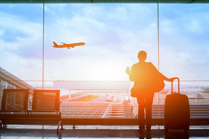 A woman standing with her carry-on suitcase and a cup of coffee watches a plane take off from an airport waiting lounge.