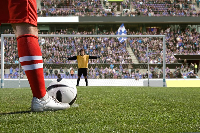 A soccer player lines up a penalty kick. We view the goalie from behind the ball.