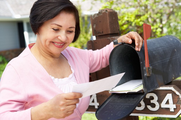 A smiling woman stands next to an open mailbox holding an envelope.