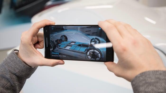A person using their smartphone to examine a concept Porsche.