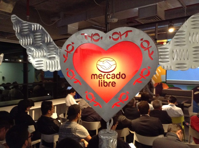 The MercadoLibre logo in a heart hovering over a crowd seated at a conference.