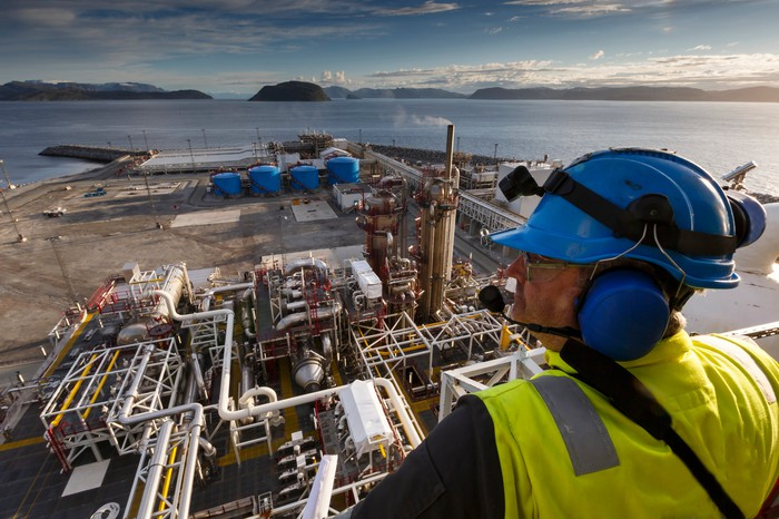 A man in a hard hat looking down over energy infrastructure next to a body of water