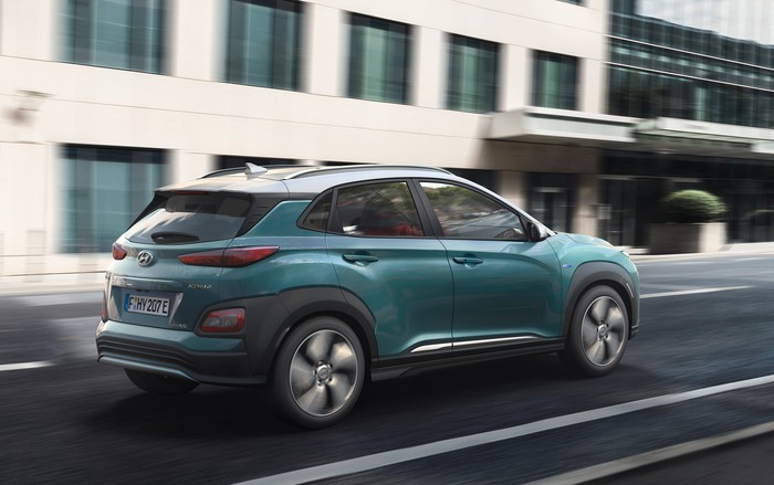A rear three-quarter view of the Kona Electric as it drives on a city street.