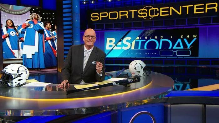 Sportscaster Scott Van Pelt sitting at a desk with ESPN Sports Center sign behind him