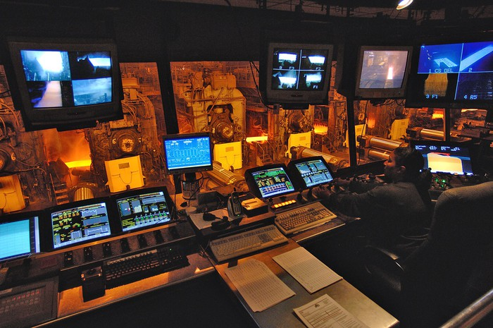Control room with monitoring equipment above a strip steel mill manufacturing floor.