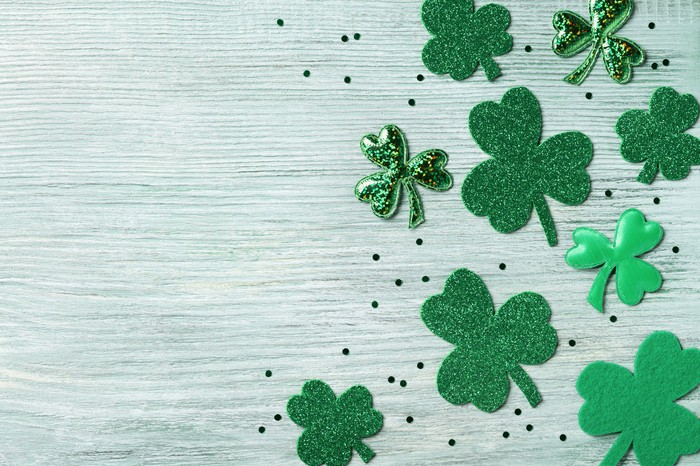Green shamrocks on a wooden board.
