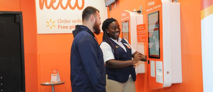 A Walmart associate helping a customer at a Pickup Tower.