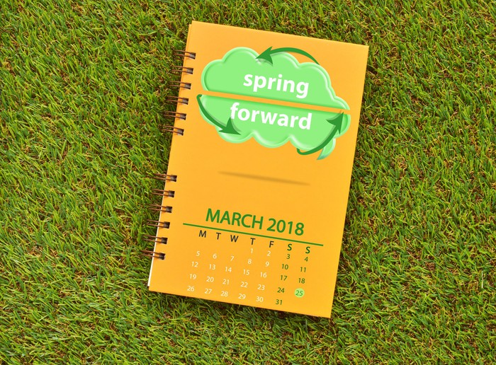 "Notebook with cover showing ""spring forward"" and a calendar of March 2018"