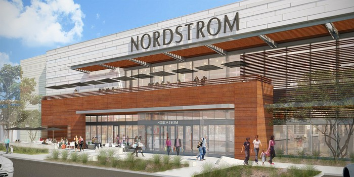 Nordstrom storefront with a terrace over the entrance with places for people to sit and people walking on the sidewalk outside in front of the store.