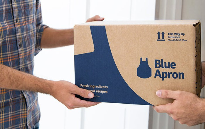 A man handing a Blue Apron meal-kit box to a customer