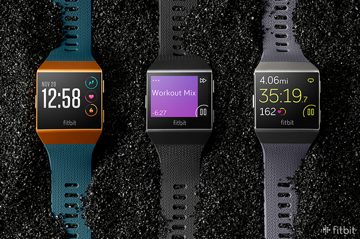 Three Fitbit Ionic smartwatches in a row on a black-and-white speckled surface