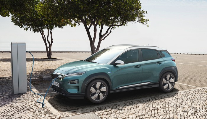 A green Hyundai Kona Electric, a small crossover SUV, parked at a charging station.