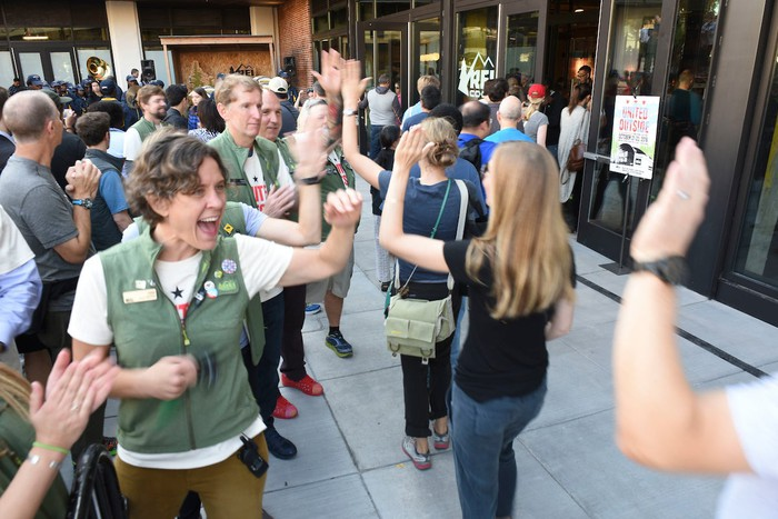 REI employees greeting customers are a store's grand opening