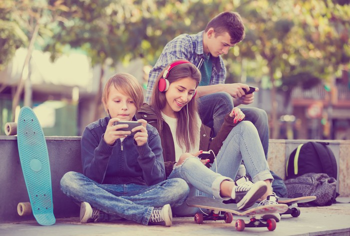 Three teenagers sitting outside, using smartphones.