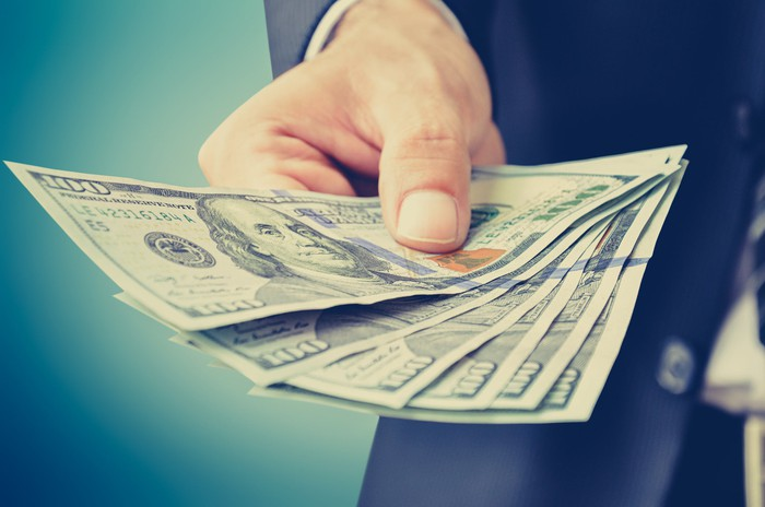 Six hundred-dollar bills fanned out in an outstretched hand.