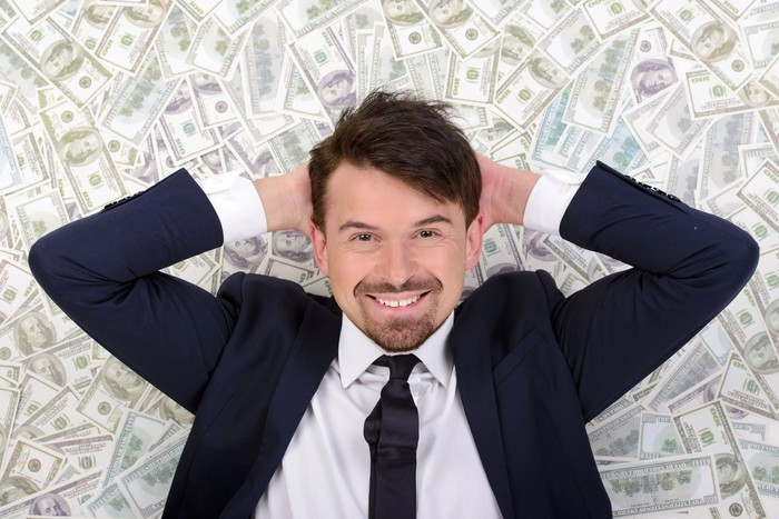 A smiling man in a suit lying on a messy pile of cash.