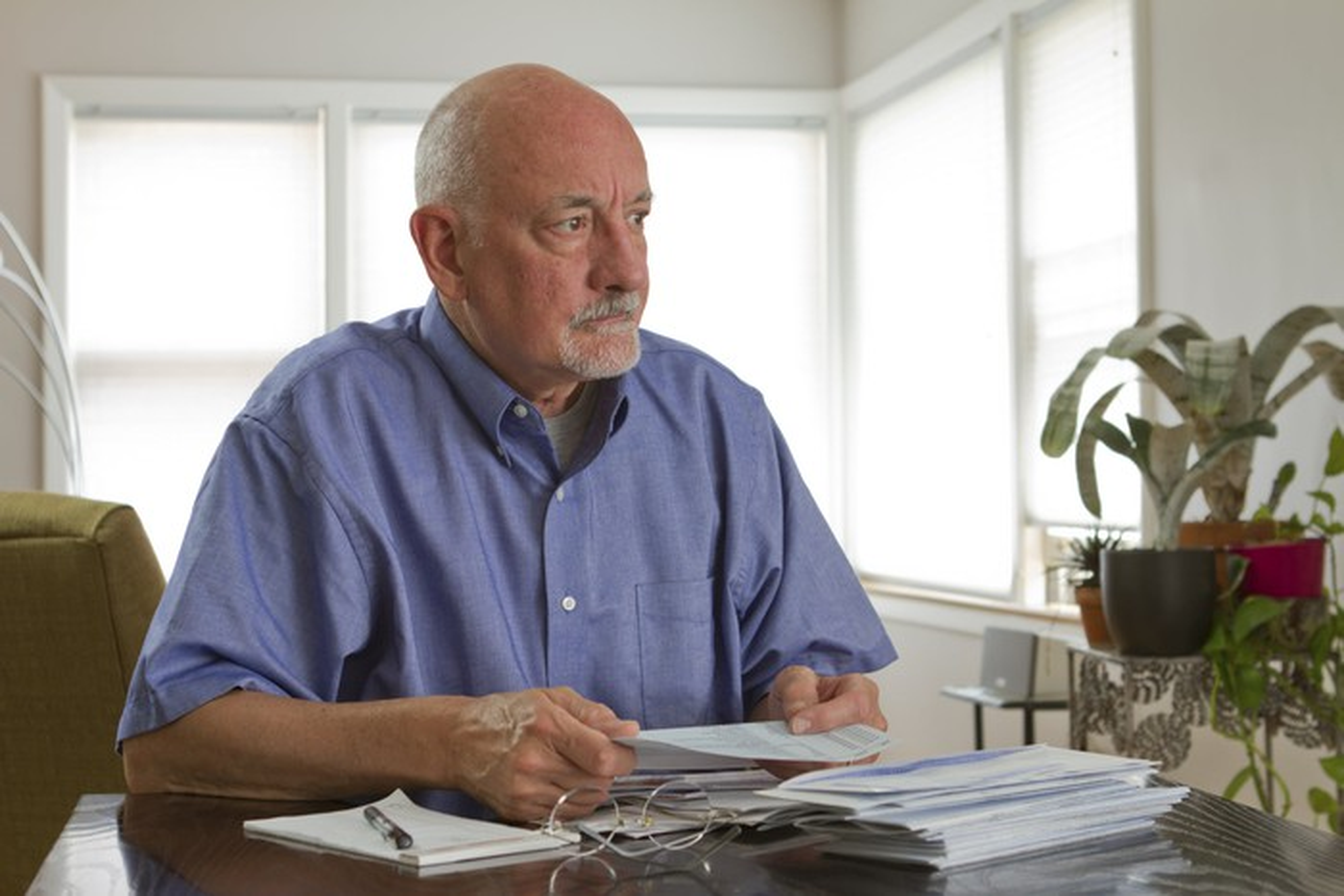 A worried elderly man examining his finances.
