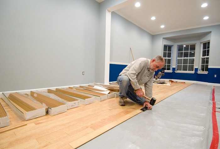 Installer laying wood laminate flooring.