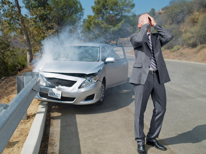 A man in a suit puts his hands on his head while standing in front of a car that crashed into a guardrail.