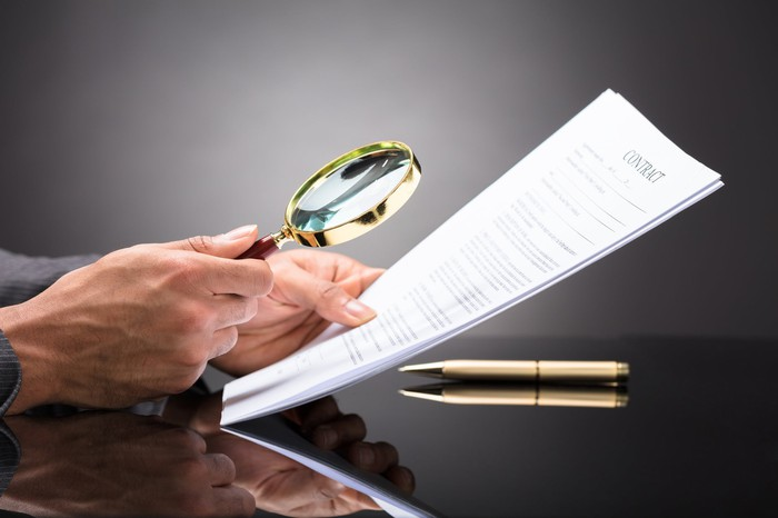 a man with a magnifying glass looking at a document