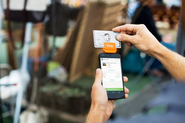 A person making an in-store payment through Etsy with a credit-card reader and mobile phone.