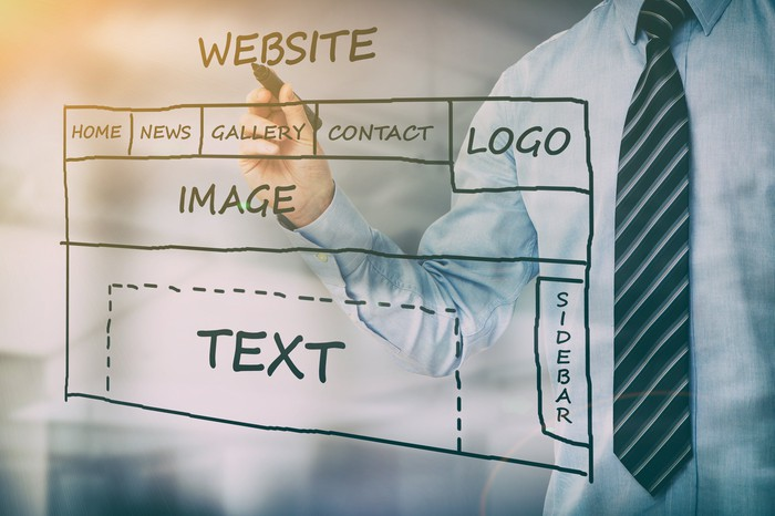 A man drawing a diagram for a website with a marker.