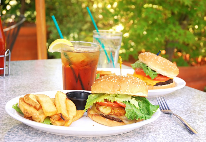 Two plates with burgers and fries on them, sitting on a table with a glass of water and a glass of iced tea, next to a fork