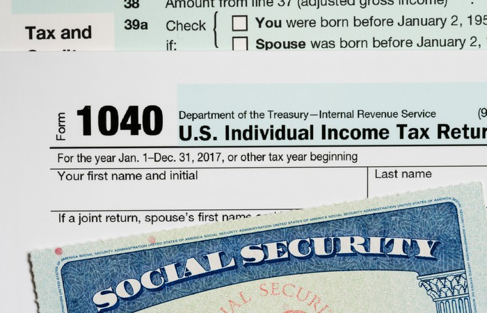 1040 tax form, stacked between tax instructions and a Social Security card.