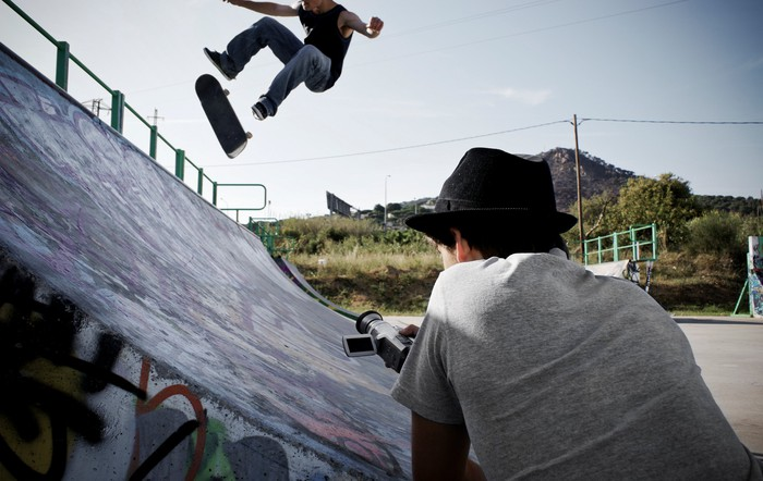 A person filming a skateboarder who is in the air doing a trick.
