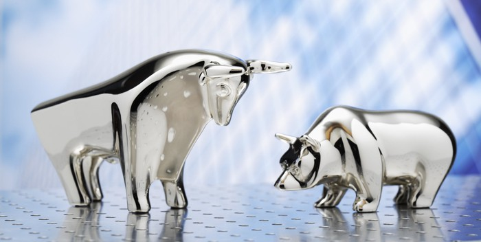 A glass bull and a bear side by side facing each other on top of a steel surface