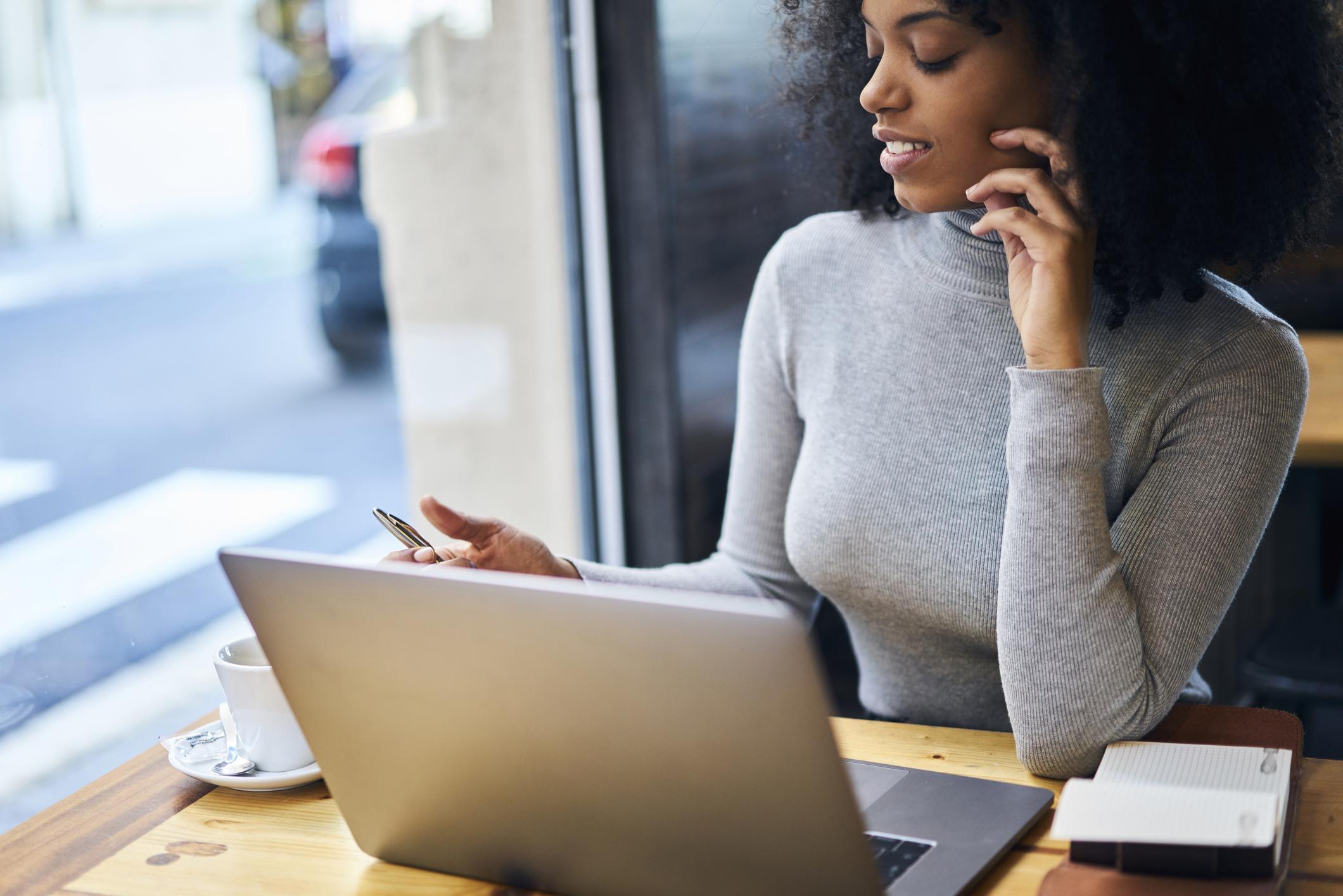 Woman at a laptop near a window