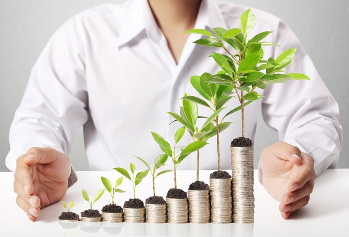 A person standing behind rising stacks of coins with growing plants on each one.