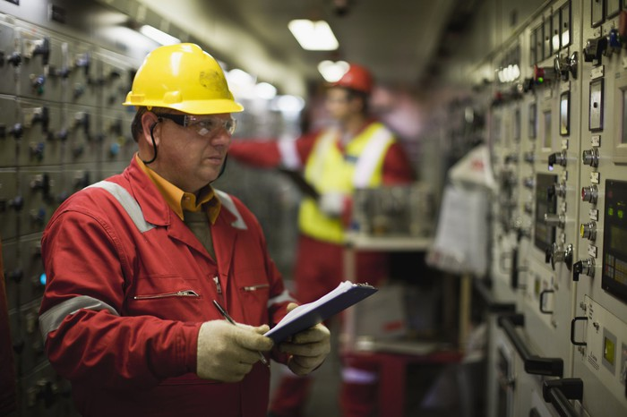 Man looking at industrial equipment while wearing a yellow hard hat and writing on a clipboard in his hands
