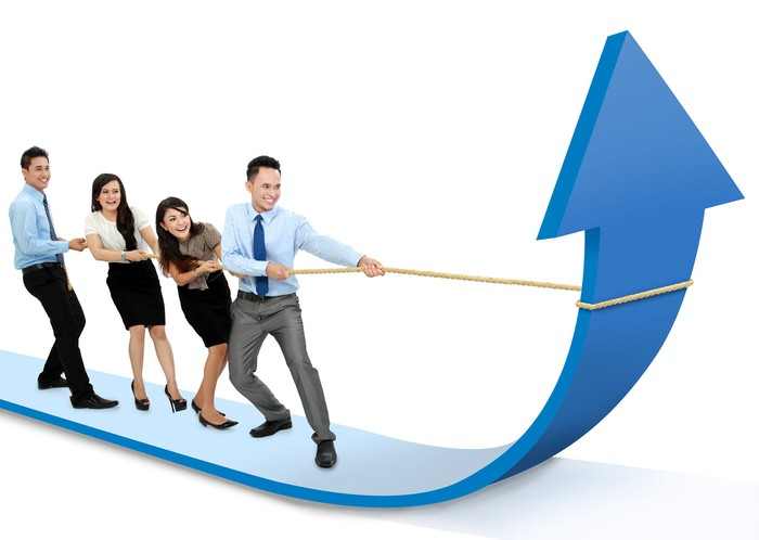 Four businesspeople tug on a rope to pull a large charting arrow upwards.
