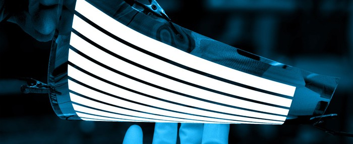 A technician demonstrates a flexible OLED screen by bending it with a simple design on the screen.