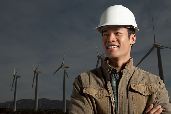 A smiling man wearing a white hard hat standing in front of wind turbines