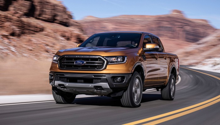 A gold 2019 Ford Ranger driving fast on a curvy road.