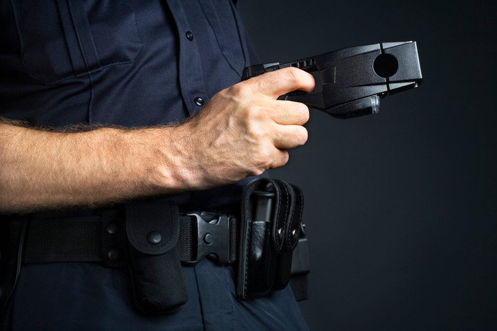 A police officer holding a Taser in his right hand