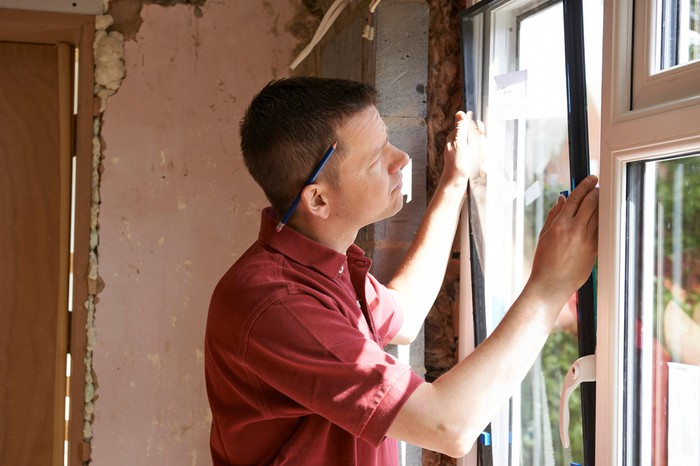 A contractor installs a window in a home.
