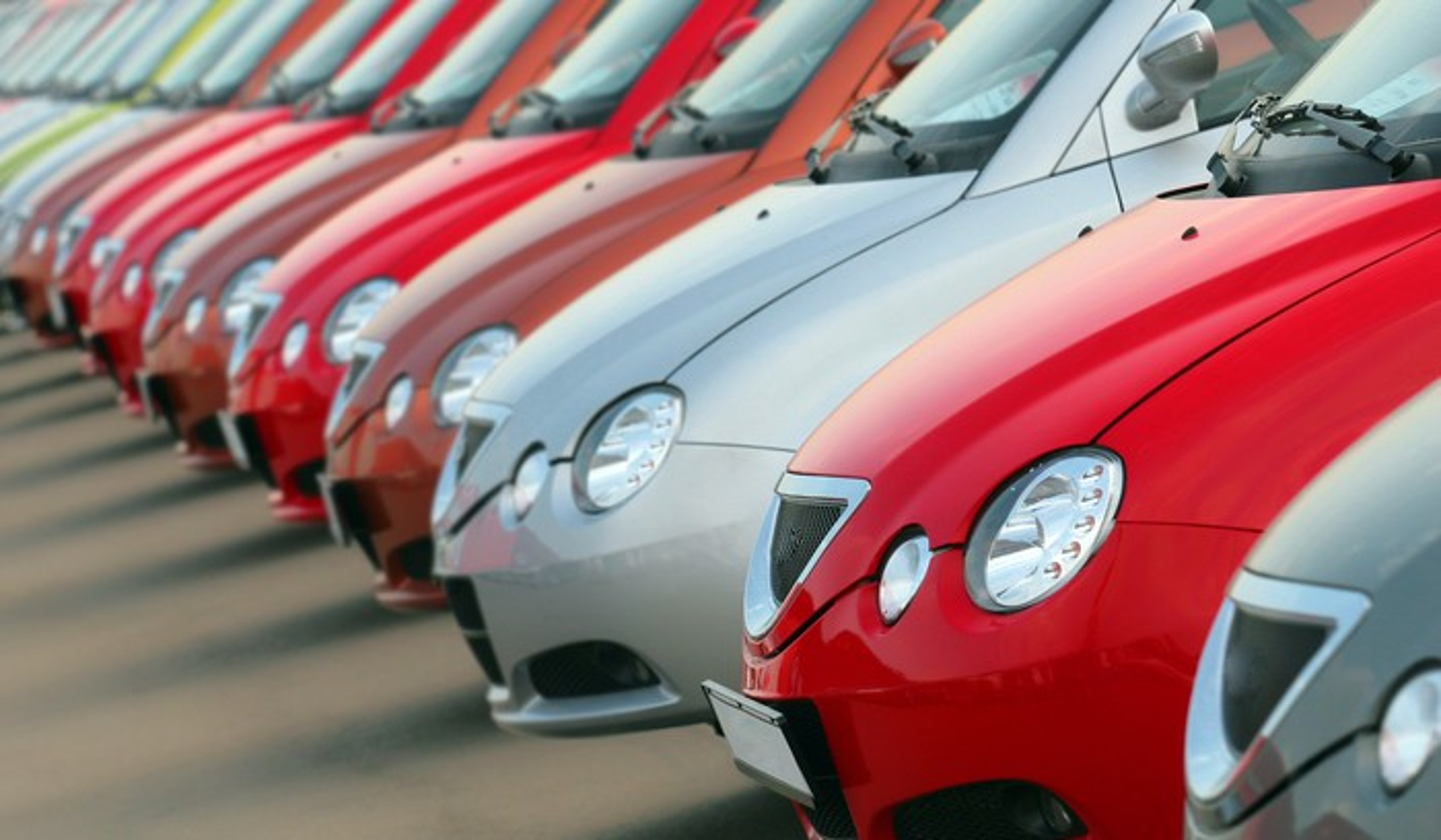 A fleet of cars in a parking lot.
