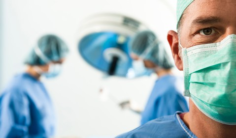 Surgeon in foreground with operation in background