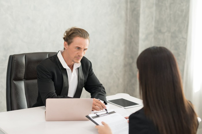 Professional man sitting across from woman at a desk.