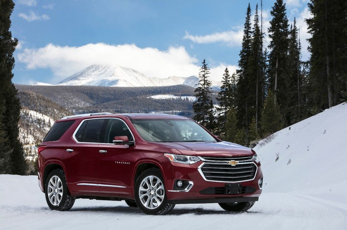 A red Chevy Traverse parked on snow, with tall trees in the background